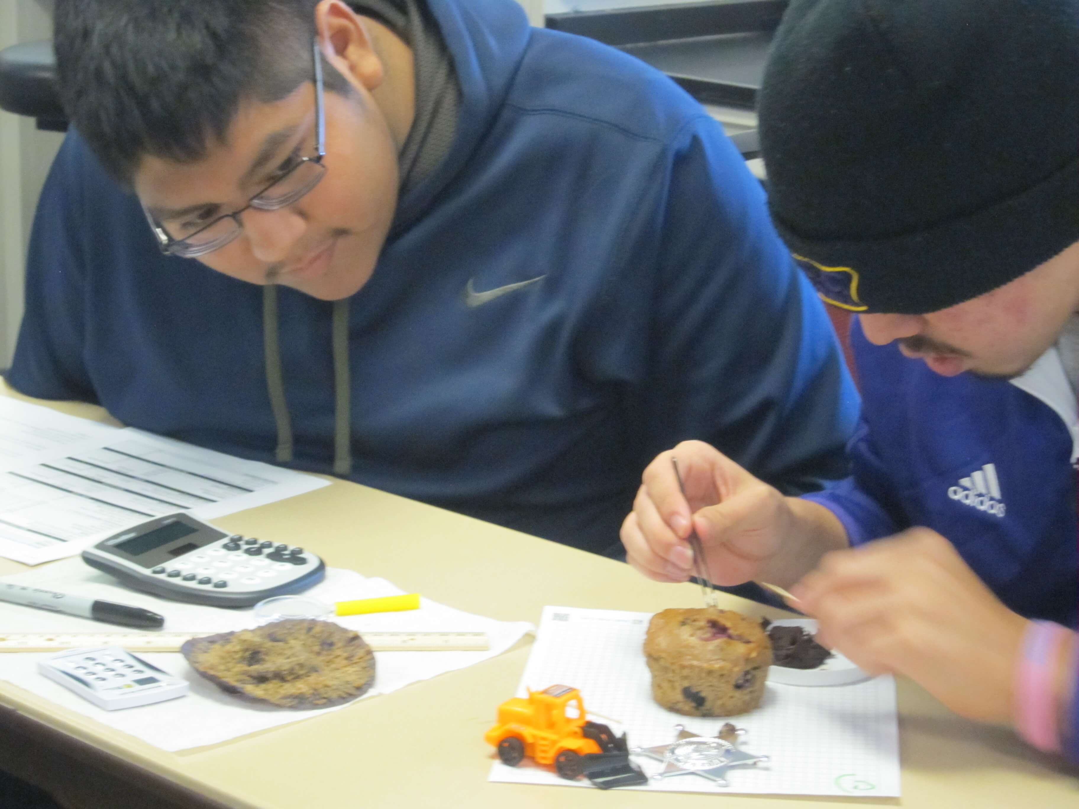 Two individuals participate in muffin mining exercise to learn about copper mining.