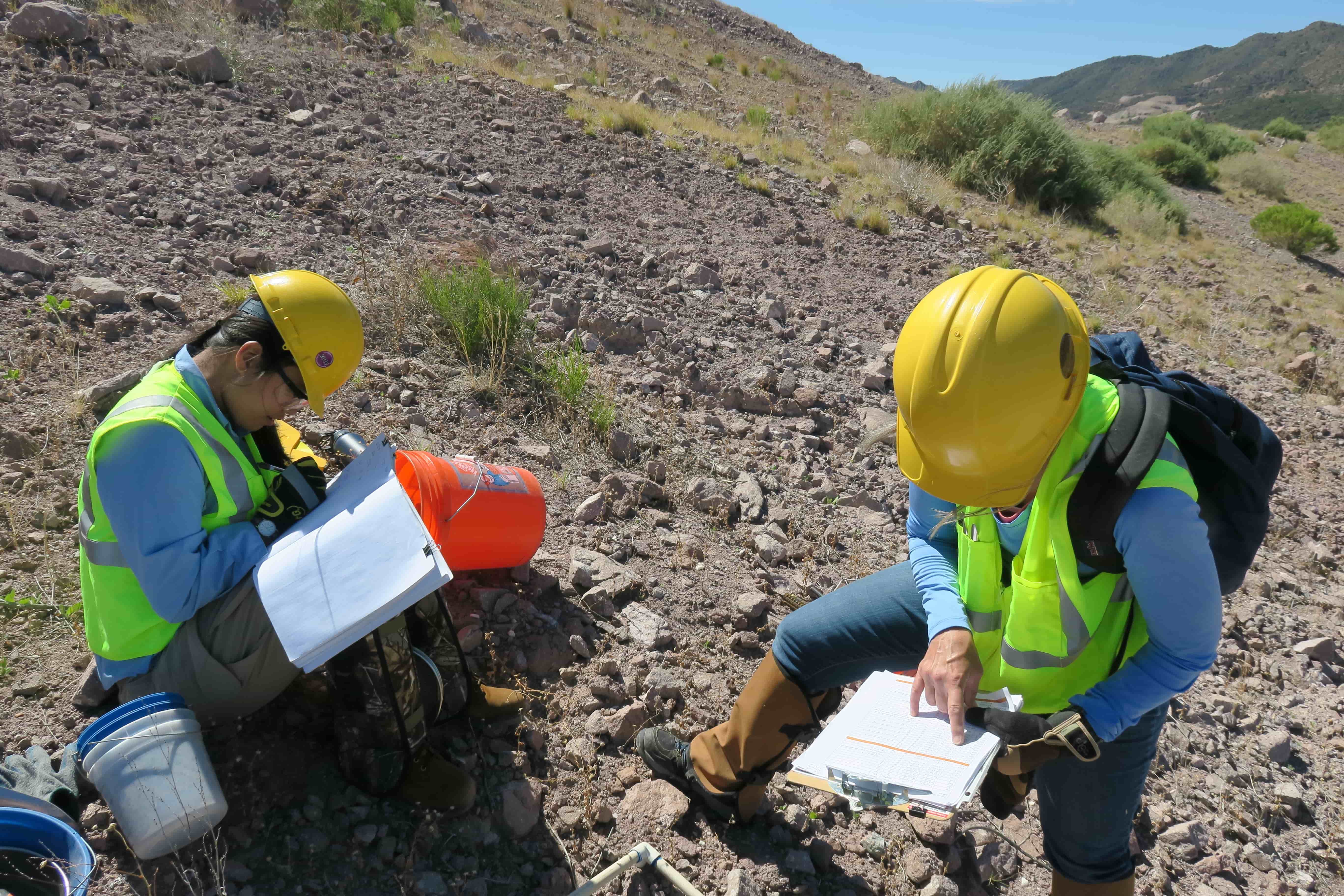 Photo of 2 scientists writing down data and checking GPS coordinates on revegetatedwaste rock slope.
