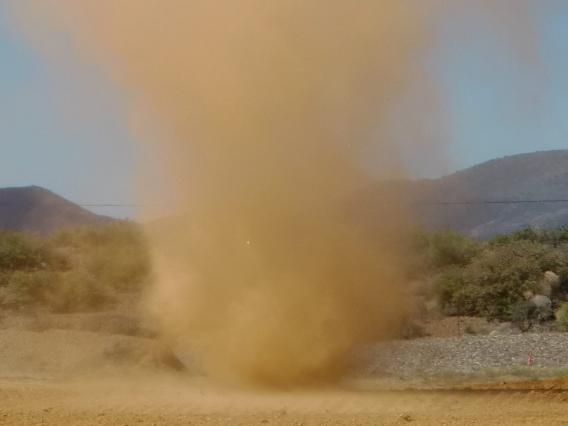 Photo of dust cloud forming over mine tailings.